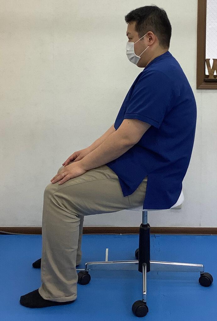 高い椅子に座っての猫背