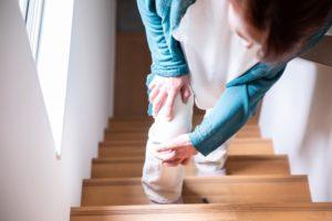 変形性膝関節症の女性が階段昇降中に膝の痛みを感じている