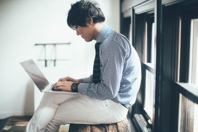パソコン作業にて脚組み座り、猫背の男性