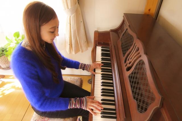 アップライトピアノを演奏する女性