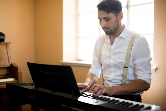 ピアノを演奏する男性です。うまく演奏できない場合は、イメージトレーニングも重要になります。