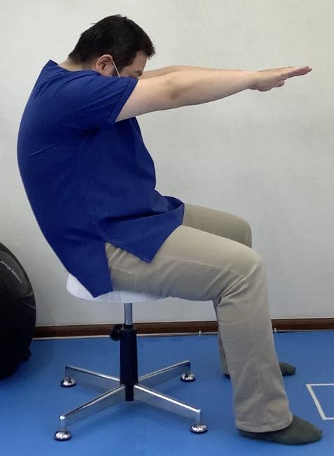 脊柱の柔軟性アップの運動の後方への動きです。骨盤を倒し、肩甲骨から両腕を突き出すようにしながら背中を後ろへ丸めます。