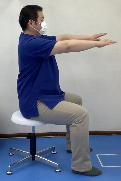 脊柱の柔軟性をアップする運動のスタートポジションです。椅子に座った状態で背筋を伸ばし、両腕を前方へ伸ばします。